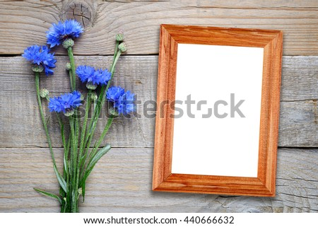 Cornflowers and photo frame on wooden background