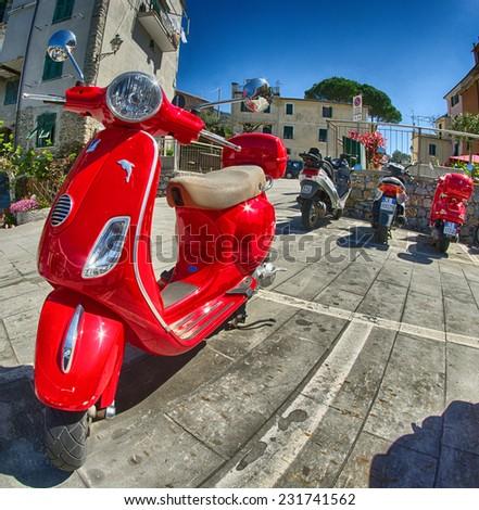 CORNIGLIA, ITALY - APR 14: Red vintage Vespa in the city streets, April 14, 2013 in Corniglia, Italy. This is the preferred way to travel in the Cinque Terre Park - stock photo