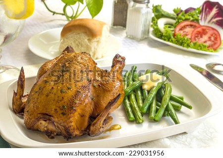 """Cornish game hen with fresh vegetables and roll ready to enjoy for dinner or lunch """"Cornish hen meal"""" - stock photo"""