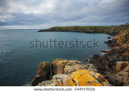 Cornwall, England: Lizard Point Lighthouse during a cloudy day; rocky coast on foreground.