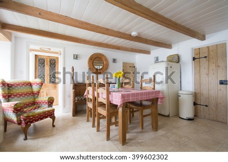 CORNWALL, UK - CIRCA JULY, 2015. An example of the interior of a typical Cornish holiday cottage kitchen with wooden furniture, ceiling beams, doors and a comfortable armchair. - stock photo