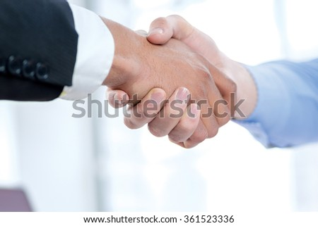 Corporate business handshake. Close-up view of a handshake while two successful businessman shaking hands at the table against each in the business office in formal wear and work at a laptop. - stock photo