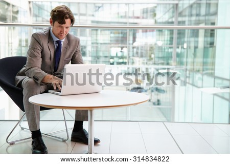 Corporate businessman using laptop computer, full length - stock photo