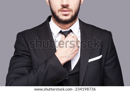Corporate confidence meets exceptional style. Cropped image of fashionable young man adjusting his necktie while standing against grey background - stock photo