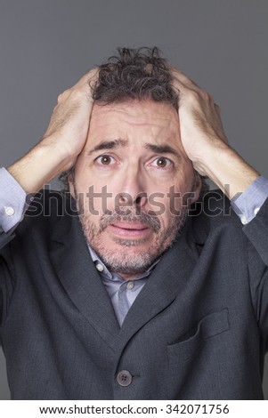 corporate despair concept - desperate 40s salt and pepper businessman holding his head for office catastrophe,studio shot - stock photo