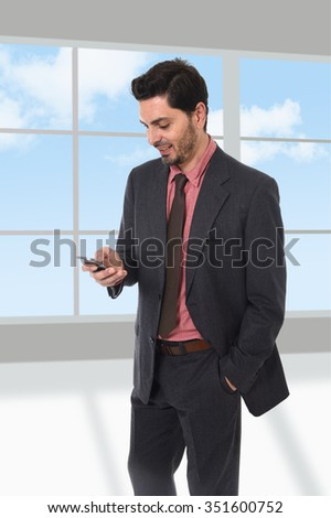 corporate full body portrait of young attractive businessman of Latin Hispanic ethnicity talking on mobile phone in suit and tie standing in front of modern office window