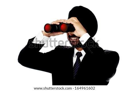 Corporate man viewing through binoculars - stock photo