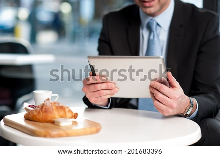 Corporate manager checking mails on his tablet device - stock photo