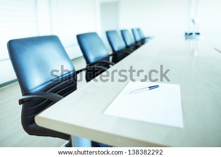corporate office chairs in a boardroom with pen and paper - stock photo