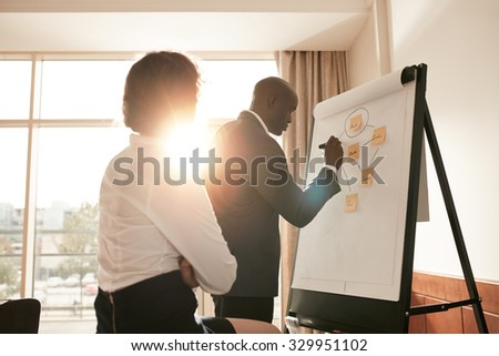 Corporate people discussing new business prospectus on flipchart. Businesspeople in conference room of a hotel working on new project. - stock photo