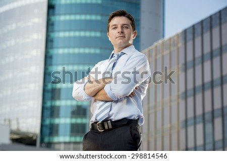 corporate portrait of young attractive businessman in shirt and tie with folded arms standing on a clean modern buildings background looking successful and confident - stock photo