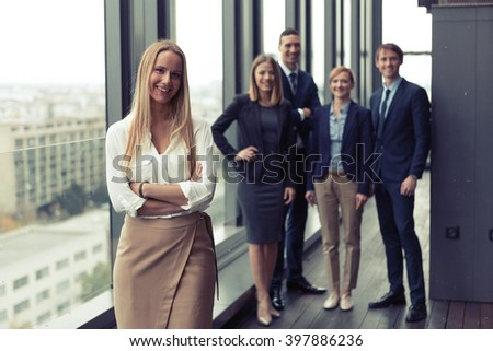 Corporate portrait of young business woman with her colleagues in background. Post processed with vintage film and sun filter.