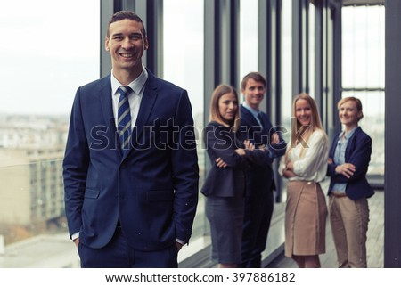 Corporate portrait of young businessman with his colleagues in background. Post processed with vintage film and sun filter.