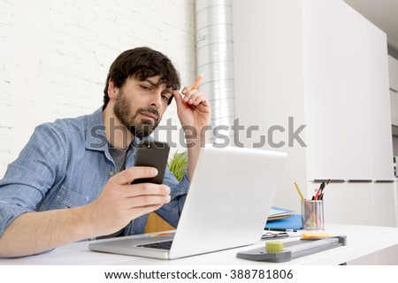 corporate portrait young Hispanic attractive hipster businessman on his 30s working at modern home office with computer laptop using mobile phone wearing casual denim shirt and beard - stock photo