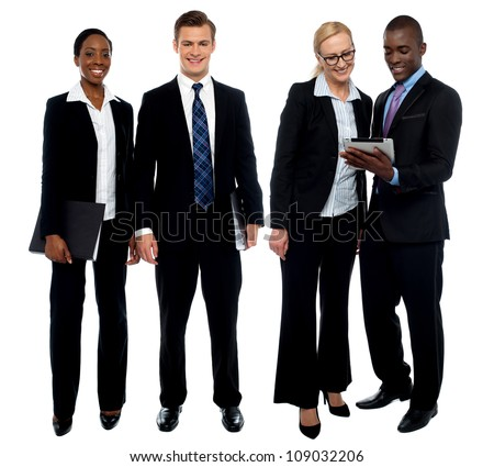 Corporate team of four posing with tablet pc. One team using tablet and other members facing camera - stock photo
