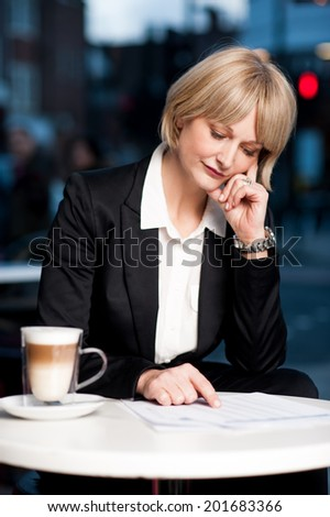 Corporate woman checking reports, hands on her head - stock photo