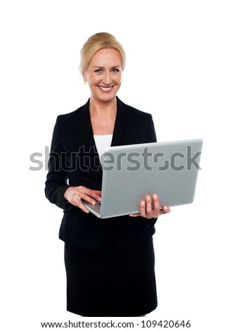 Corporate woman holding laptop and looking at camera - stock photo