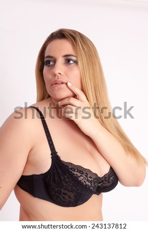 Corpulent, busty woman with long blond straight hair and black bra in thought / Corpulent, busty woman with long blonde hair and black bra - stock photo