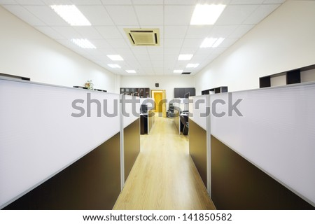 Corridor and empty working areas with desktops separated by partitions in office. - stock photo