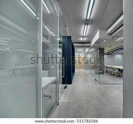 Corridor between work zones in the office in a loft style. Zones are fenced with mesh, glass and concrete partitions. Lamps are glowing. On the back there is a light brick wall and light wooden doors.