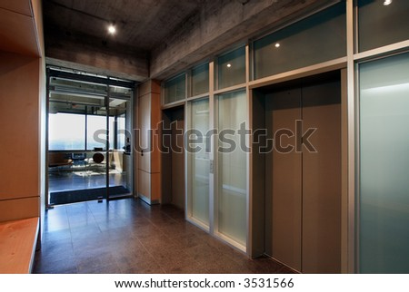 Corridor in a modern office environment, elevator doors, bright lit window, glass walls