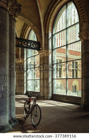 Corridor in a museum building with large windows and a bicycle parked near the column. - stock photo