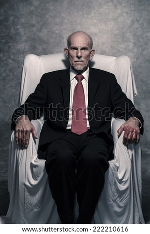 Corrupt businessman with bloody hands sitting in white chair. Gray beard wearing dark suit and red tie. Against grey wall. - stock photo