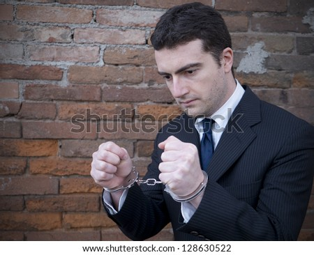 corrupted manager in jail with handcuffs - stock photo