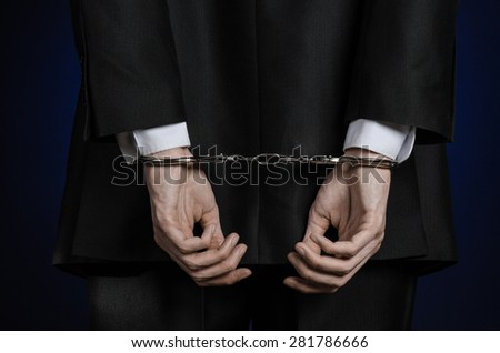 Corruption and bribery theme: businessman in a black suit with handcuffs on his hands on a dark blue background in studio isolated view from the back - stock photo