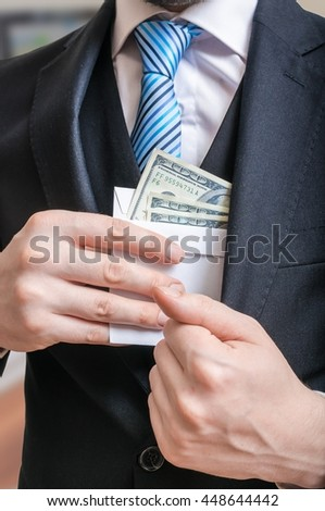 Corruption concept. Businessman is hiding letter full of money or bribe in suit jacket. - stock photo