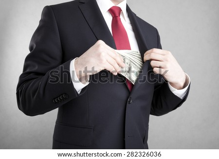 Corruption. Man putting money in suit jacket pocket. - stock photo