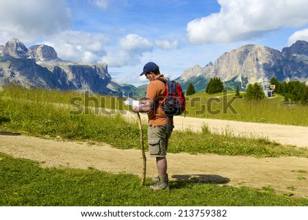 CORVARA ITALY-AUGUST 08, 2014: a man checks his map surrounded by the rocky Dolomites mountains, in Corvara.