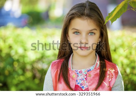 Cose up, Beautiful little girl on green background of summer city park - stock photo