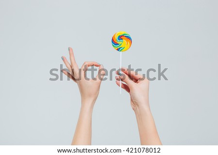 Coseup portrait of female hands holding lollipop and showing ok sign with fingers isolated on a white background - stock photo