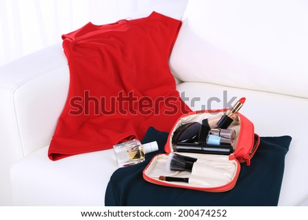 Cosmetic bag, fashion clothes, bottle of perfumes on sofa on light background - stock photo