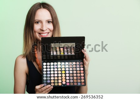 Cosmetic beauty procedures and makeover concept. Woman holds makeup professional palette. Make-up applying. Green background