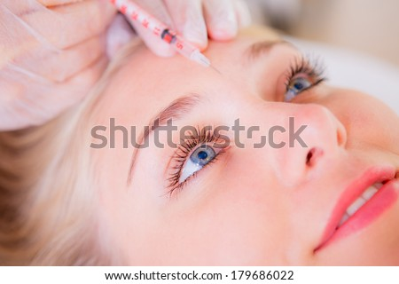 Cosmetic botox injection in the female face, eye and eyebrow zone - stock photo