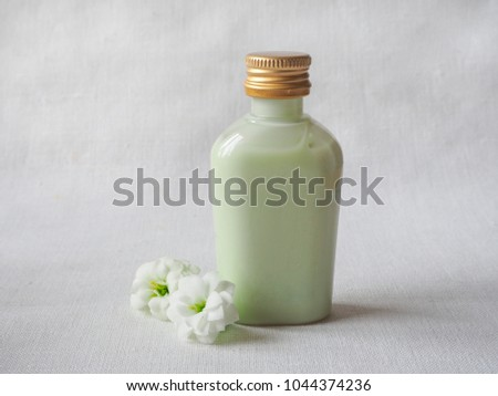 Cosmetic bottle container with white flowers. Natural organic beauty product concept.