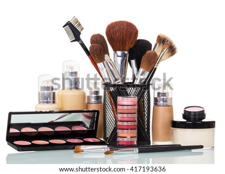 Cosmetic brushes, liquid foundation, lip gloss, blush and cream bank isolated on white background.