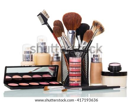 Cosmetic brushes, liquid foundation, lip gloss, blush and cream bank isolated on white background. - stock photo