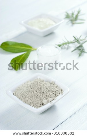 cosmetic clay and bath salt on white wooden table