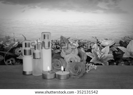 cosmetic container and candle on blur black and white florist on ocean background