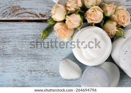 Cosmetic cream with flowers and spa stones on wooden background - stock photo