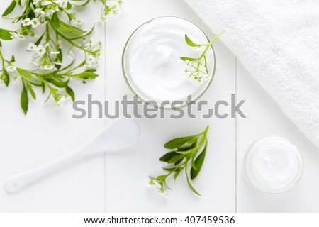 Cosmetic cream with herbal flowers hygienic skincare product wellness and relaxation medical mask in glass jar on white background - stock photo