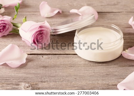 cosmetic cream with pink roses on old wooden table - stock photo