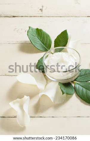 cosmetic cream with white rose petals on bright wooden table