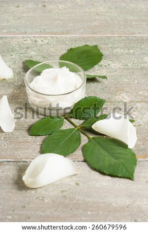 cosmetic cream with white rose petals on old wooden table