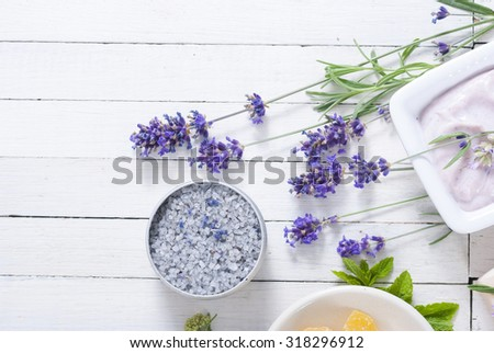 cosmetic creams, lip balm, soap and bath salt with herbal flowers on white wooden table