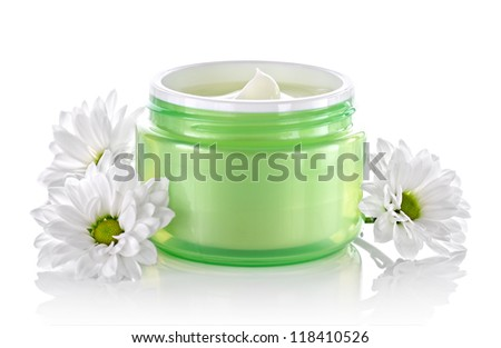Cosmetic face cream container with white daisies - stock photo