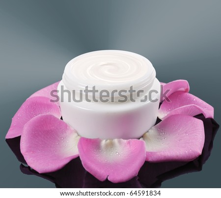 cosmetic face cream on a grey background with rose petals - stock photo